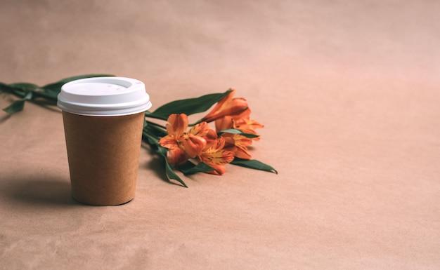 Taza de café y alstromeria sobre un fondo artesanal