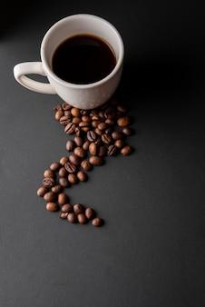Taza de café de alto ángulo con granos tostados