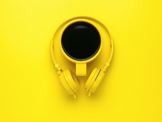 Taza de café amarilla y auriculares amarillos sobre un fondo amarillo brillante.