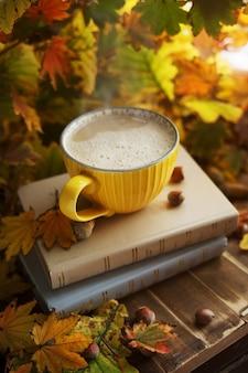 Taza de café amarilla en una pila de libros en follaje otoñal con bellotas y nueces. ambiente otoñal.