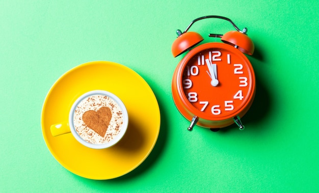 Taza de café amarilla y reloj rojo en el verde