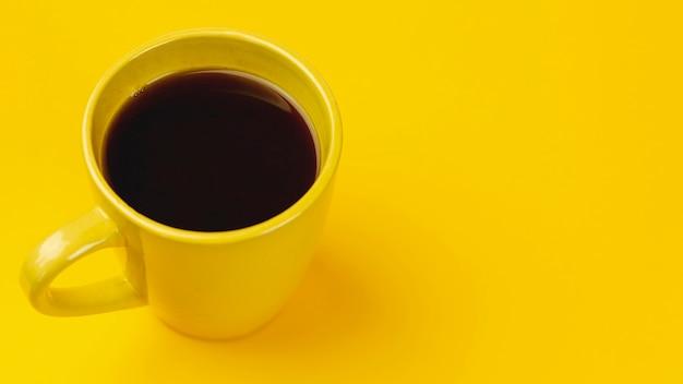 Taza de café amarilla sobre un fondo amarillo