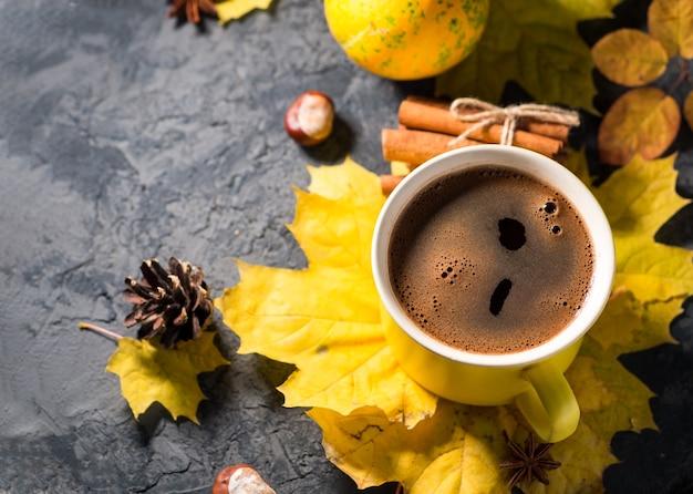 Taza de café amarilla sobre la mesa de piedra oscura con hojas de otoño y ramitas de canela