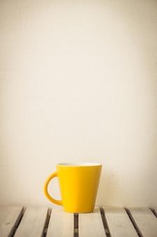 Taza de café amarillo en mesa