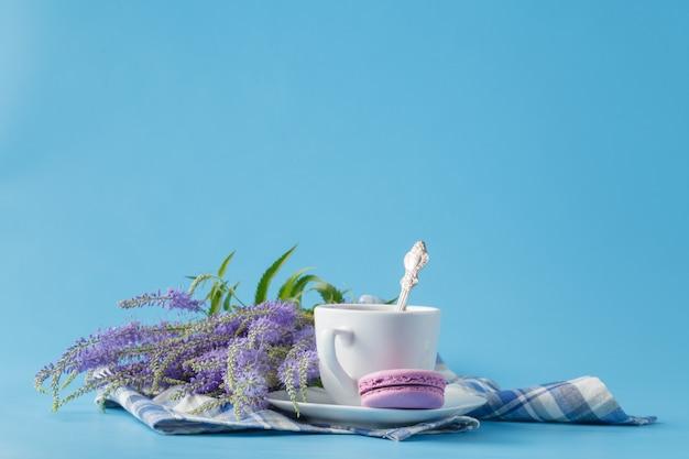 Una taza de café americano de la mañana con macarons franceses sobre fondo azul.