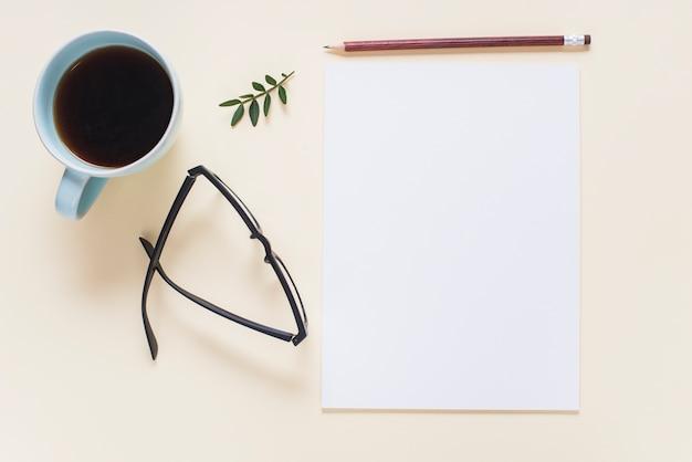 Taza de café; los anteojos; ramita; lápiz y página en blanco en blanco sobre fondo beige.