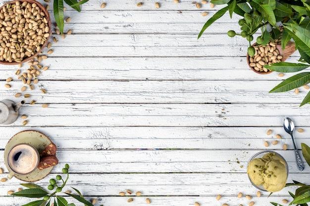 Taza de café, aperitivos y postres sobre fondo blanco de madera