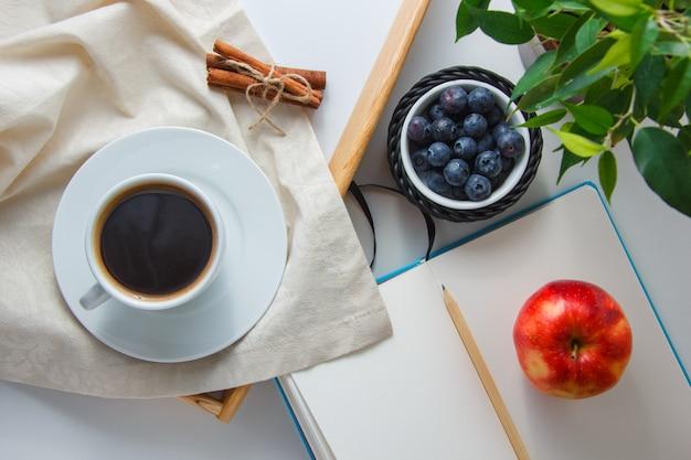 Una taza de café con arándanos, manzana, canela seca, planta, lápiz y cuaderno vista superior sobre una superficie blanca
