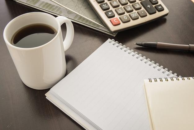 Taza de café, archivo de documento, pluma, calculadora, bloc de notas en mesa de madera