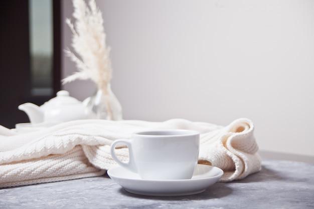 Taza de café de aroma caliente y tela escocesa blanca de punto y tetera blanca sobre la mesa gris