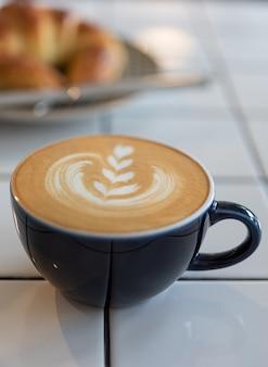 Taza de café de arte latte y croissant en mesa blanca