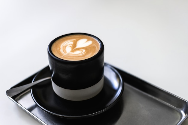 Taza de café con arte latte en forma de corazón.