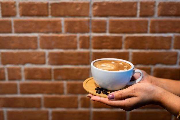 Taza de café de arte latte en manos con fondo de pared de ladrillo
