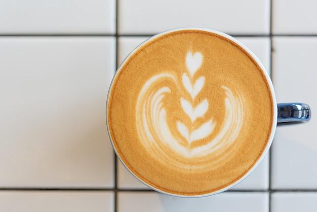 Taza de café de arte latte en mesa blanca, vista superior
