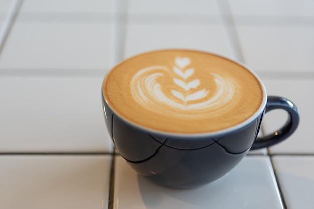 Taza de café de arte latte en mesa blanca