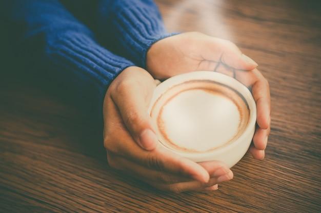 Taza de café asimiento de la mano