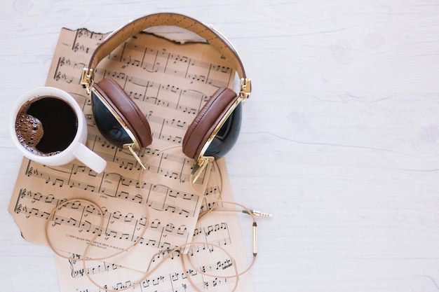 Taza de café y auriculares cerca de partituras