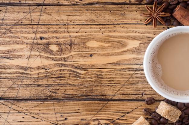 Taza de café, azúcar moreno y canela con anís en madera.