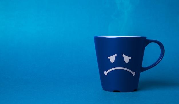 Taza de café azul con una cara triste dibujada. concepto de lunes azul