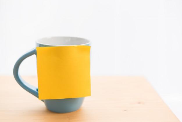 Taza de café azul y post-it en la mesa de madera