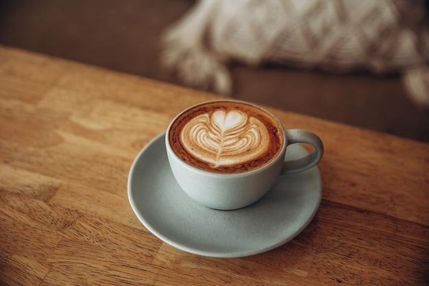 Taza de café azul sobre fondo blanco rústico con hermoso arte latte