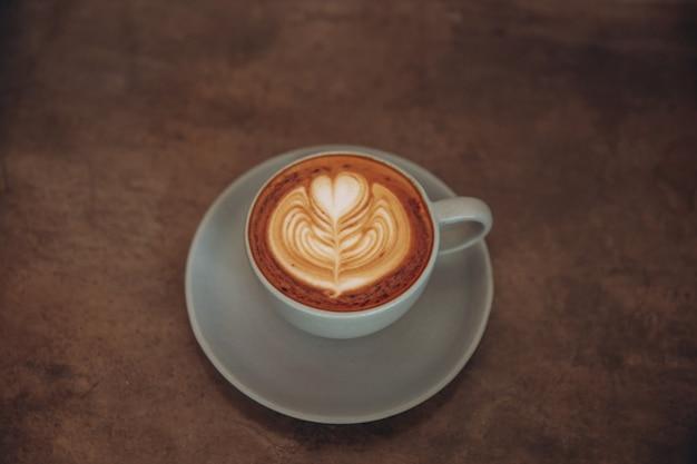 Taza de café azul sobre fondo rústico de hormigón con hermoso arte latte