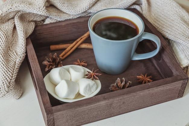 Taza de café en bandeja de madera rústica, malvavisco dulce y suéter de lana cálido