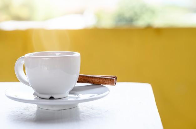 Taza de café blanca en mesa blanca con fondo amarillo