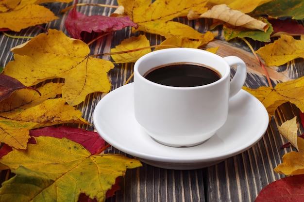 Taza de café blanca en la mesa de madera y hojas amarillas de otoño alrededor.