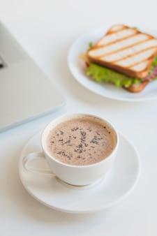Taza de café blanca con sandwich sobre fondo blanco