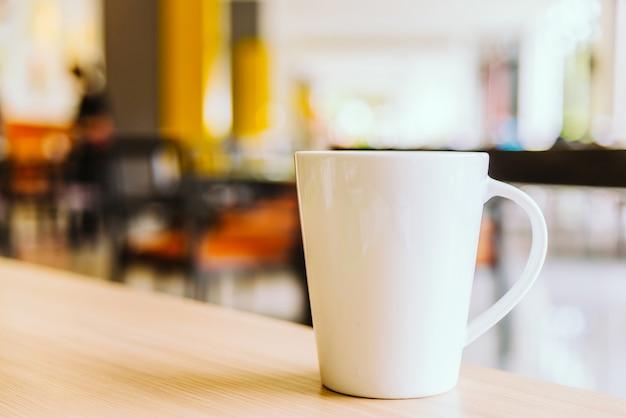 Taza de café blanco en la cafetería