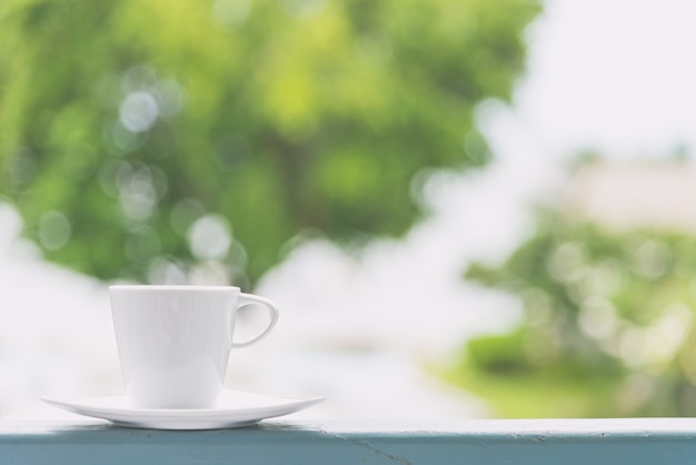 Taza de café blanco con fondo de vista exterior - efecto de filtro vintage