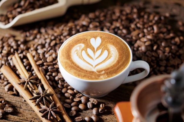Taza de café blanco y granos de café tostados alrededor.