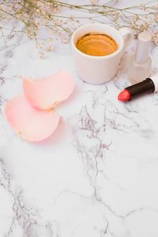 Taza de café blanco; pétalos de rosa; botella de esmalte de uñas; aliento de bebé flores y lápiz labial sobre fondo blanco con textura