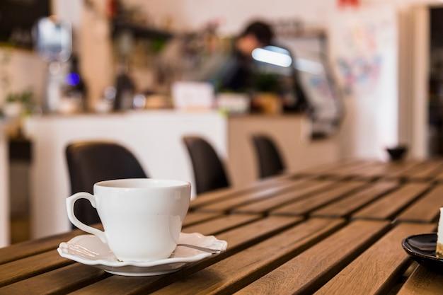 Taza de café blanco y platillo sobre la mesa de madera en la barra de café