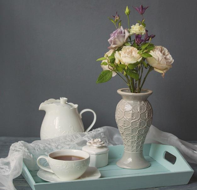 Una taza de café blanco, tetera y jarrón de flores.