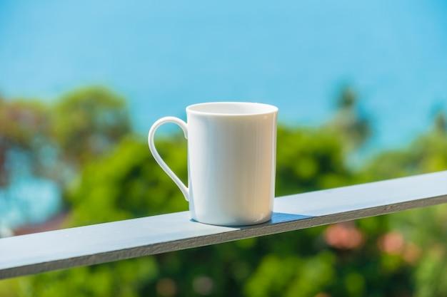 Taza de café blanco con vista al mar.