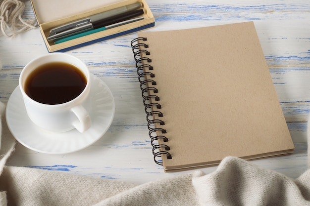 Taza con café, bloc de notas, bolígrafos en la vieja mesa de madera blanca. concepto de primavera