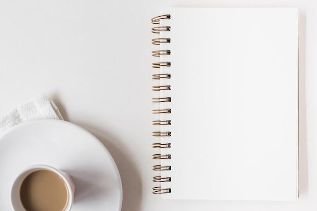 Taza de café y bloc de notas espiral en blanco sobre fondo blanco