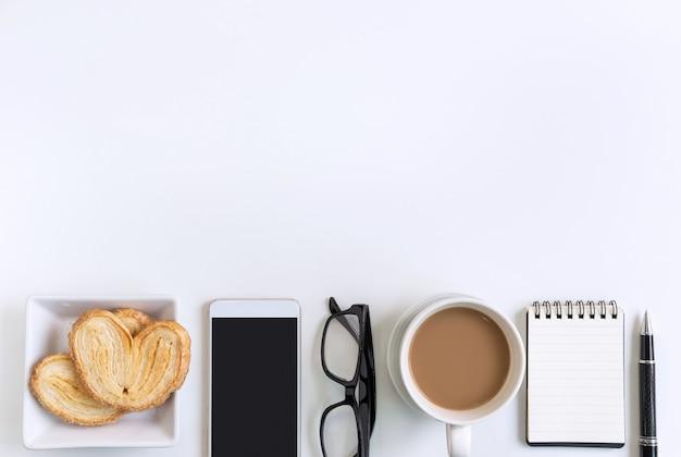 Taza de café con bocadillos, teléfono móvil y notebook en la oficina de escritorio con espacio de copia