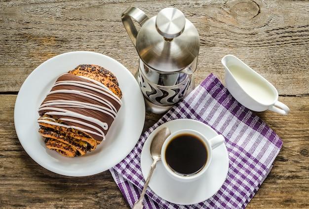 Taza de café y bollo de amapola glaseado con ganache