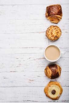 Taza de café con bollos dulces en mesa de luz