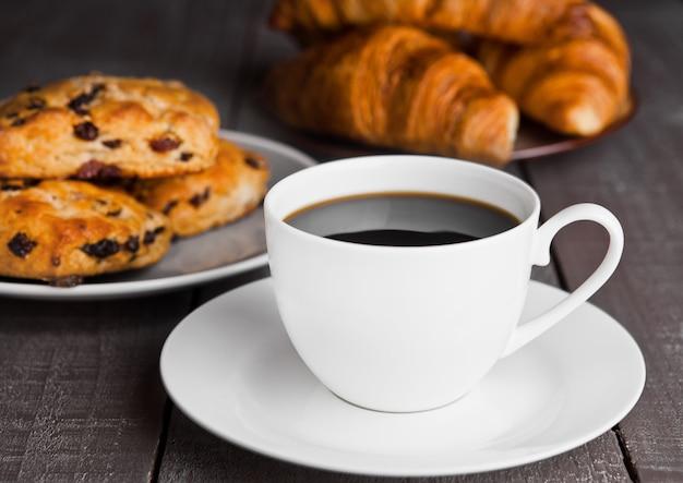Taza de café con bollos frescos y cruasanes en mesa de madera