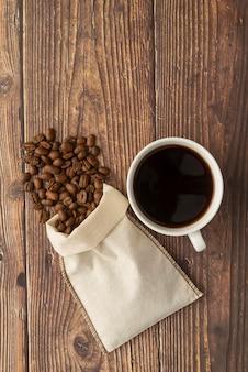 Taza de café y bolsa de tela con granos de café.