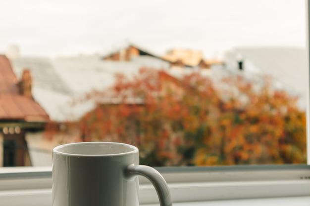 Taza de café en el borde de las ventanas en la mañana.