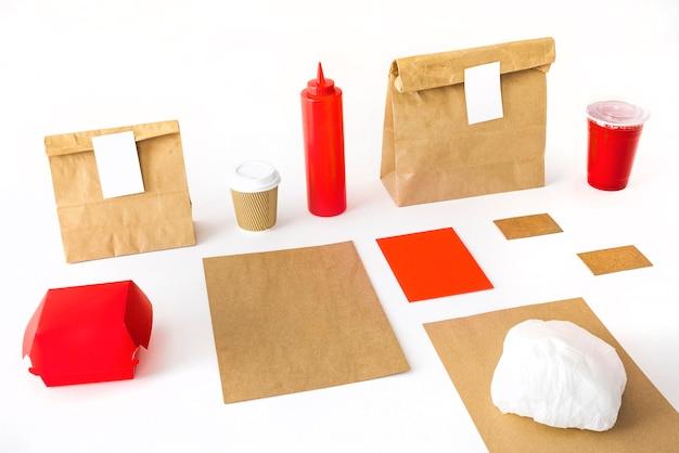 Taza de café; botella de salsa; beber; hamburguesa y paquete sobre fondo blanco