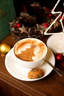 Una taza de café con café con leche arte del árbol de navidad