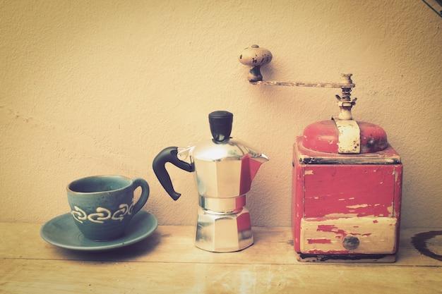 Taza de café con una cafetera y un molinillo