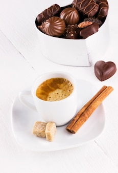 Taza de café y caja de bombones sobre un fondo blanco de madera