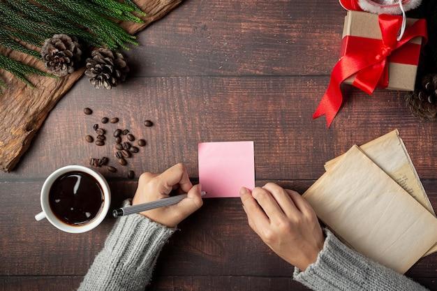 Taza de café y caja de regalo junto a la mano de la mujer está escribiendo la tarjeta de felicitación